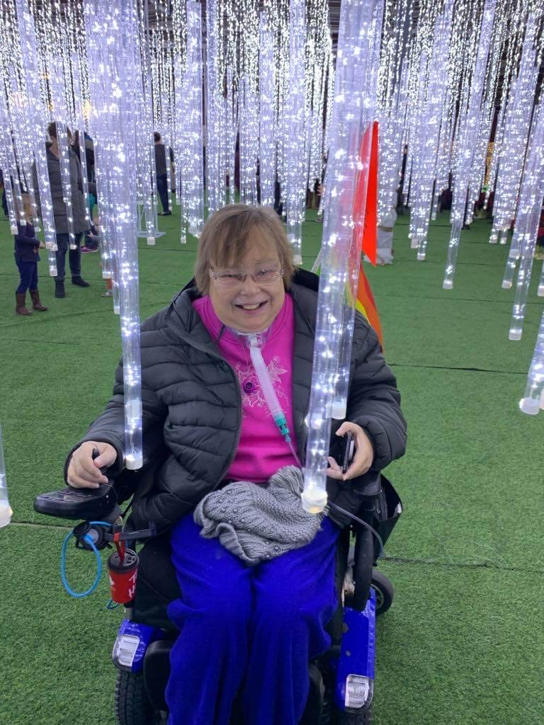 Senior woman in wheelchair in icicle forest at Glow Park
