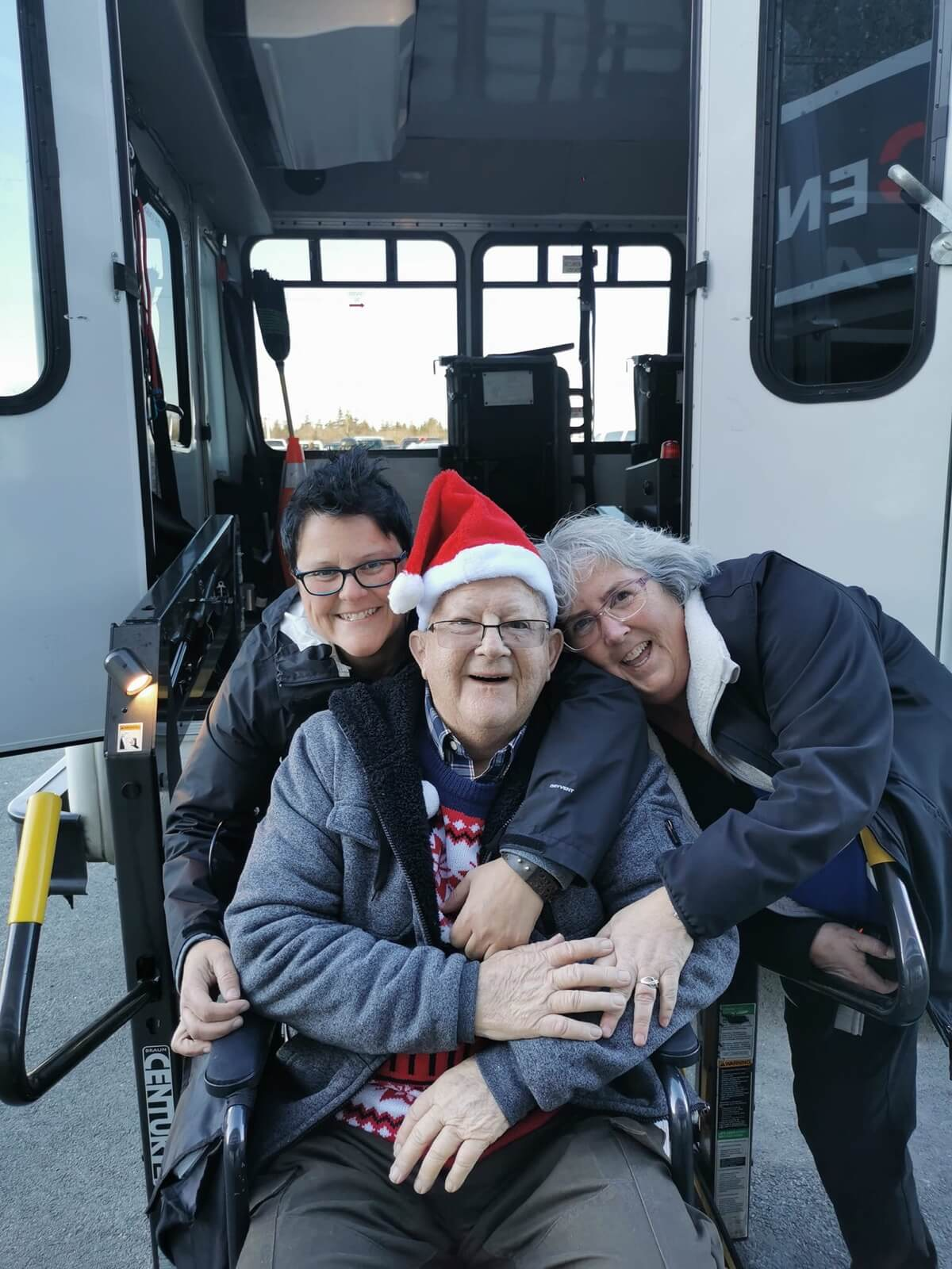 Susan and Dianne posing with male client in wheelchair on accessible bus ramp
